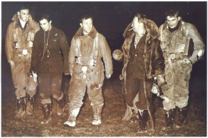 "Aircrew returning from a reconnaissance and leaflet dropping mission. Berkeley Denis Cayford is on the far left. Second from the right, with the full-length coat, is Thomas Gilbert Mahaddie (""Hamish"" Mahaddie). He was born in Scotland in 1911 and joined the Royal Air Force in 1928. Tension and fatigue of returning from an operational mission - but also the relief to be back home safely - is visible on the crewmembers' faces."